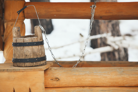 Old wooden bucket standing on the edge of the wooden well Foto de archivo