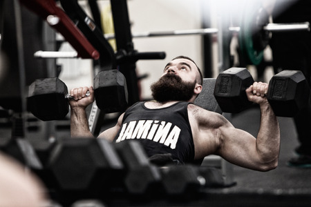 Bodybuilder working out in a gym lying on his back lifting weights Stock Photo