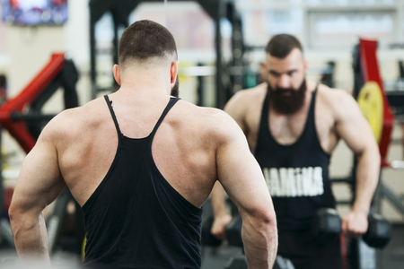 Bodybuilder with a beard working out in the gym weights Foto de archivo