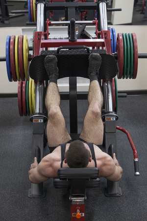Bodybuilder working out in a gym lying on his back lifting weights Foto de archivo