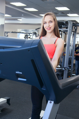simulator: Beautiful young girl engaged in fitness in the gym. Brunette performs exercises on the simulator.