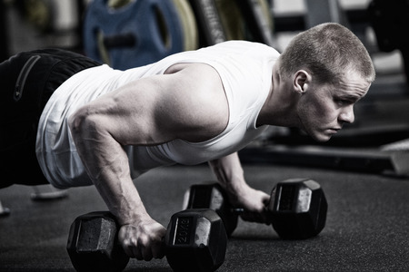 Man doing push up holding dumbbell at the gym Foto de archivo