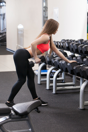 muscle gain: Beautiful young girl engaged in fitness in the gym. Brunette performs exercises on the simulator.