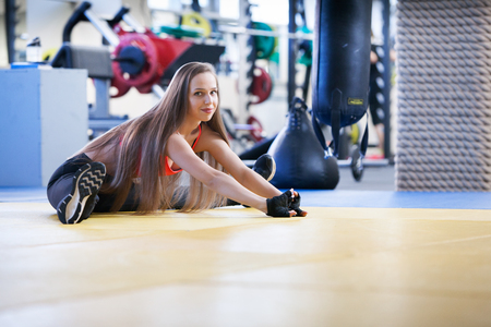 Beautiful young girl engaged in fitness in the gym. Performs exercises on the simulator.