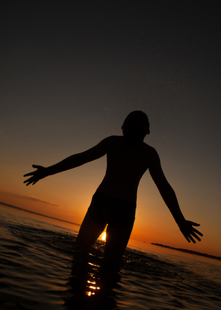 boy emotions hands at sunset in water