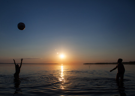 Photo children playing ball in the water at sunset. Foto de archivo
