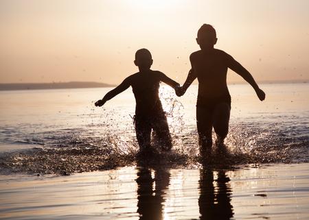 Photo children run along the water at sunset. Foto de archivo