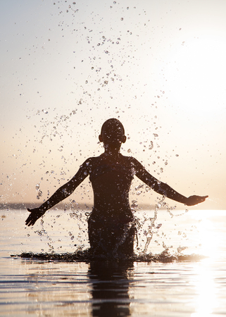 A young boy splashes water at sunset