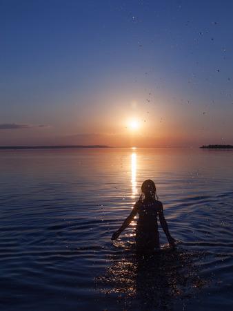 girl emotions hands at sunset in water Foto de archivo
