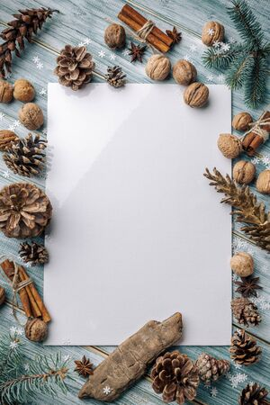 Christmas background. Spruce and pine branches on a light vintage wooden background of boards. Cones nuts spices in the decor. Christmas. The view from the top. Christmas decorations. Space for text.