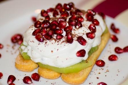 Closeup of pomegranate piaces, cream, kiwi and cookie photo