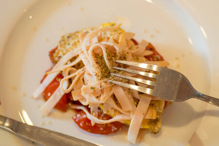 Upper view of a meal with ham and tomatoe with knife and fork photo