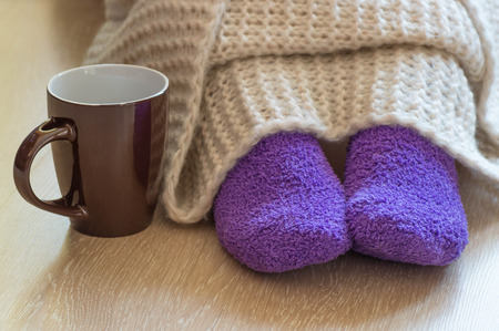 Cold concept with teacup near the legs which are covered with fluffy warm blanket and wearing fluffy warm purple socks