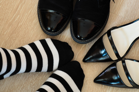 wearer: Dilemma concept where the black and white striped socks wearer stand between the with elegant black leather shoes and an elegant black leather high heel shoes