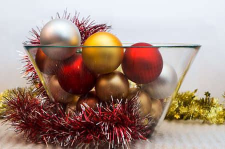 fragile peace: Different color Christmas tree decorations are in a glass bowl Stock Photo