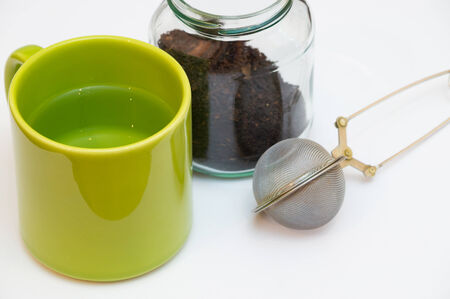 tea infuser: Empty tea infuser and a jar of tea next to each other with a green cup which contains liquid. Stock Photo