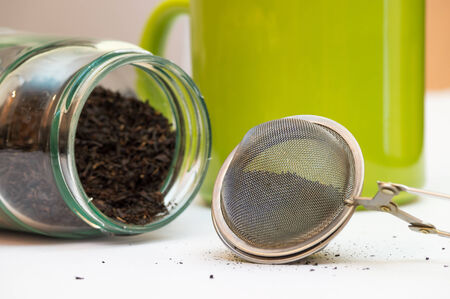 tea infuser: Macro show of the filled tea infuser, felt down jar with tea inside and a green cup in the background Stock Photo