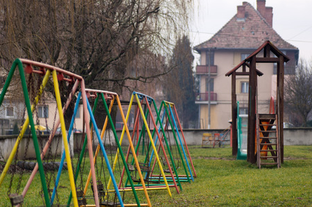 Old aged playground with swings and slide photo
