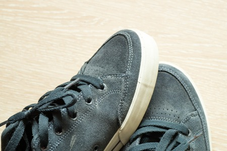 trouser legs: Close up shot of a left sneaker being on the right sneaker Stock Photo