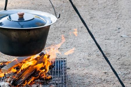 under fire: Fuego que arde bajo el caldero Foto de archivo