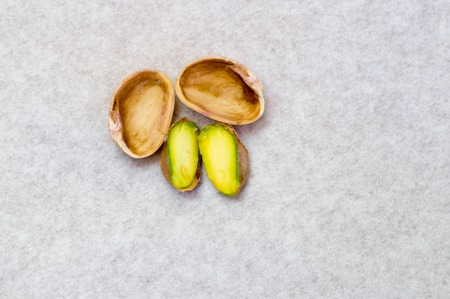 Upper shot of opened pistachio nut and its shell