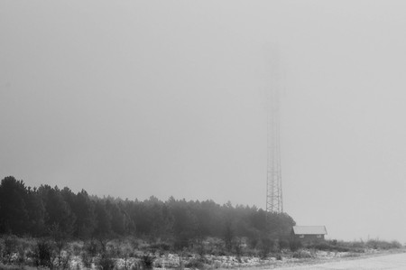Radio tower next to a house in foggy weather