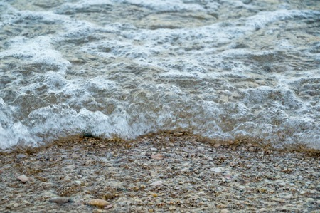 Water waves with bubbles on rocky shore Stock Photo