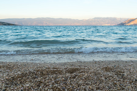 Water waves with distant mountains and shore