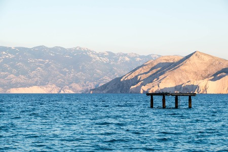 Sea with distant hill and concrete platform Stock Photo