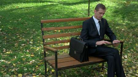 businessman sitting on a bench in the autumn with the tablet
