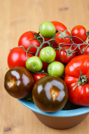 Various types of tomatoes in a bowl on the table photo