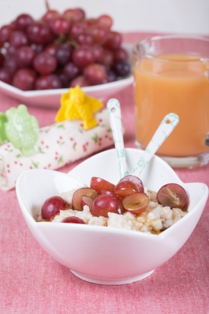 Oatmeal with maple syrup, grape and juice photo