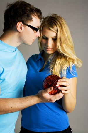 young man in glasses and beauty blond girl holding red ball for christmas tree Stock Photo - 7423442
