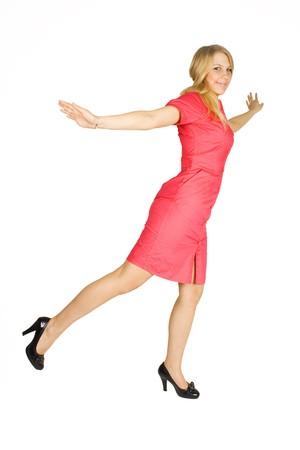 tacones negros: chica de la belleza rubia en vestido rojo y negros talones mirando la c�mara, de pie sobre una pierna aislada en blanco  Foto de archivo