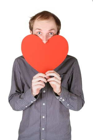 dignified: young man in grey shirt holding big red paper heart and looking out of it, half body, isolated Stock Photo