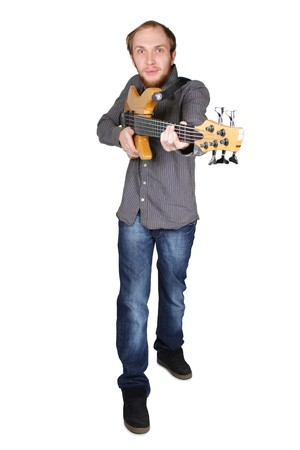 young man with beard in grey shirt and jeans playing bass guitar and pointing for fingerboard at front, full body, isolated photo