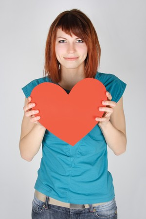 young redhead girl smiling and holding red paper heart, looking at camera, half body photo