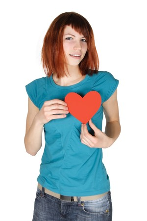 young redhead girl holding red paper heart on her breast, looking at camera, half body, isolated photo