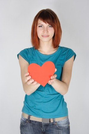 young redhead girl holding red paper heart, looking at camera, half body photo