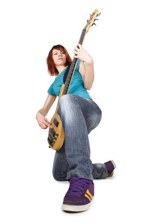 young beauty redhead girl sitting on one knee and playing bass guitar, full body, isolated photo
