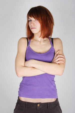 dissatisfaction: young redhead girl in purple shirt with crossed hands, dissatisfaction emotion, half body