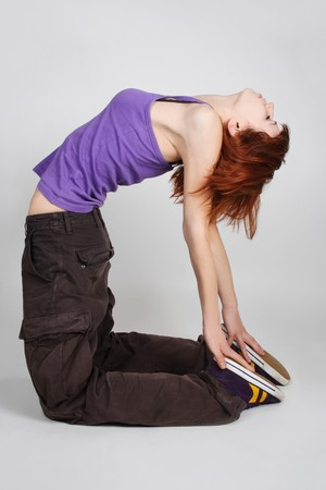 lean back: young redhead girl in hip-hop clothes standing on knees and bending back, hands on feet, full body Stock Photo