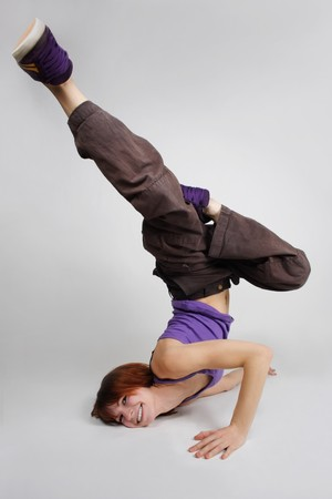 break in: young redhead girl in hip-hop clothes making freeze, break dance position with head over heels, full body