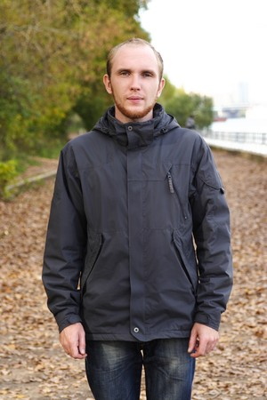 young man with beard standing on path in autumn park, half body photo