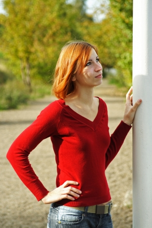 young redhead girl outdoor, hand on pole, looking at side Stock Photo