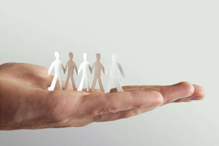 concep: human holding little paper cutout people, team and friendship concep