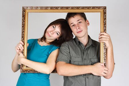 man and woman holding gold decorative frame and standing inside it Stock Photo - 8621510