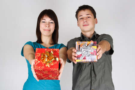 young brunette girl and man offer gifts to camera and smiling photo