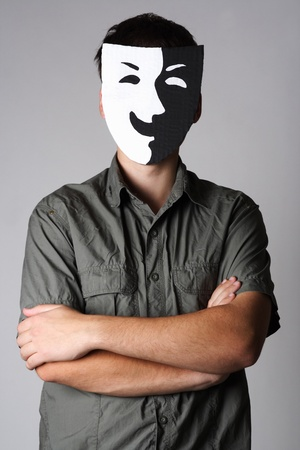 insincerity: man in theater black and white smiling mask standing with crossed hands