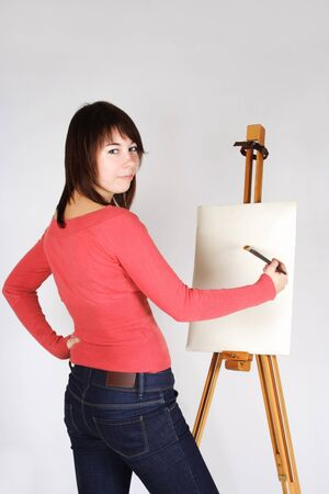 young girl in red shirt standing near easel, painting and looking back photo